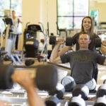 woman assisting man sitting on bench lifting dumbbells