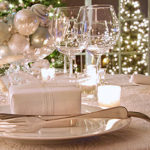festive table with plate silverware glasses and lighted tree with ornaments all in white