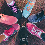 circle of peoples feet in tennis shoes touching toes together
