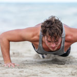 man doing pushup on sand at beach