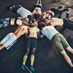 circle of people in elbow plank on floor with heads together