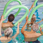 people doing water exercise with foam noodles