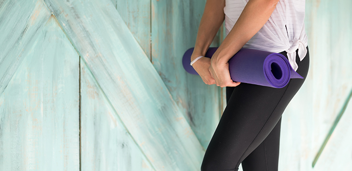 woman in yoga clothes holding rolled up mat