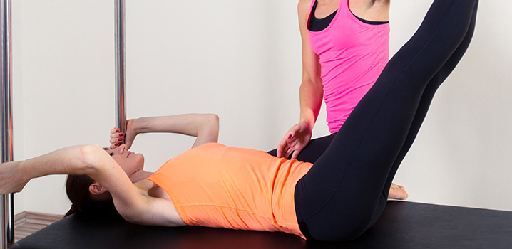 woman helping another woman with positioning on reformer