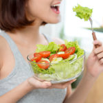 close up of woman eating fresh salad with fork
