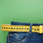 blue jeans waist with measuring tape wrapped through belt loops