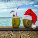 Santa hat on coconut cocktail at beach
