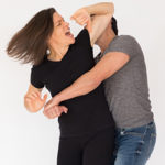 woman elbowing man in head as he grabs her from behind
