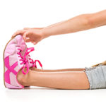 child's legs sitting on floor with pink tennis shoes and hands reaching to hold toes