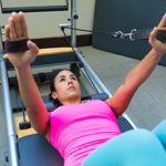 woman with hands in straps reclining on reformer