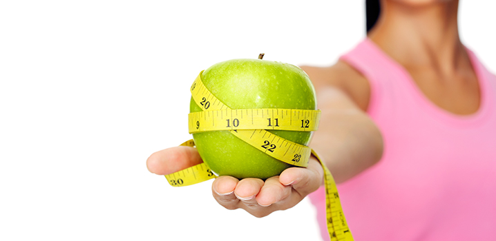 woman holding green apple with tap measure wrapped around it