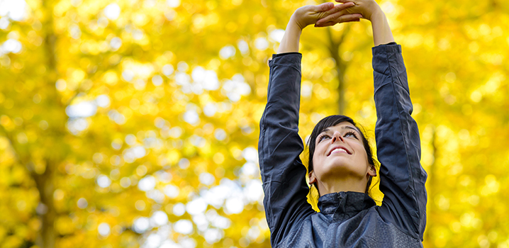 woman stretching arms overhead in grove of yellow trees