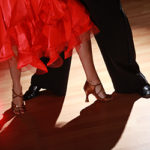 close up of man and woman's legs dancing Salsa on dark background