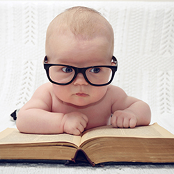 cute baby in glasses reading a book