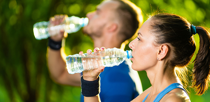 man and woman drinking water from bottle after exercise