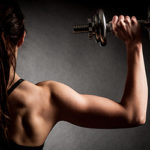 back view of muscular woman lifting with dumbbell