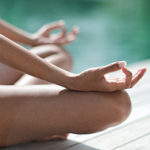 woman's legs sitting on dock with hands in mudras on knees