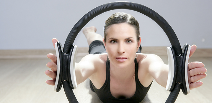 woman on belly on floor looking through pilates hoop