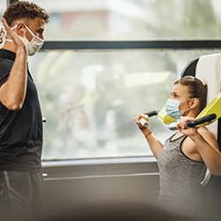man and woman personal training socially distanced with masks