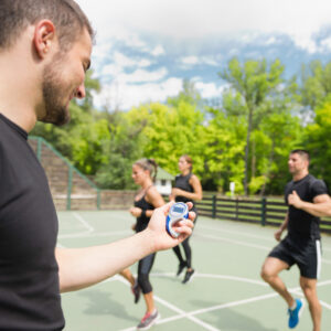 Sports trainer with stopwatch cardio training outdoors